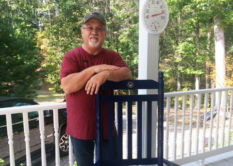 Mr. Crum shows off his new rocking chair on his porch in North Carolina. The chair was a retirement gift from the JHS faculty and staff.