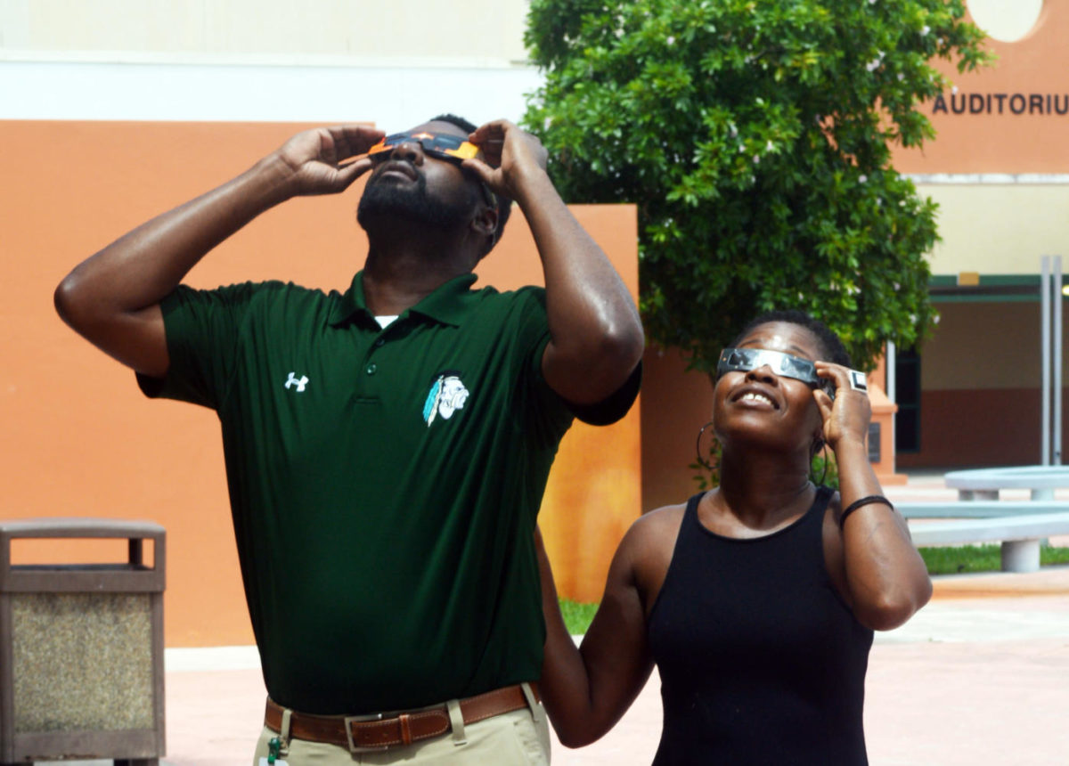 Teacher Sherman Steele and School Counselor Shaun Hutton view the eclipse in Jupiter Highs courtyard with special glasses to shield the eyes from harmful rays.