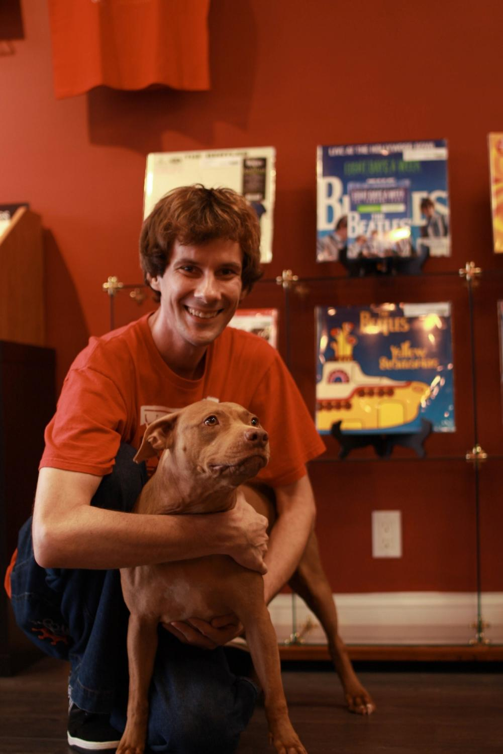 Tom Procyk and his dog Lea in front of their Beatles collection.