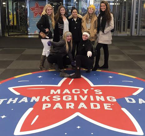 "Kayleigh Sternberg, Lindsey Fine, Kaitlynn Partridge, Sarah Parker, Sierra Witchey, Kaya Mancini and Marissa Viele pose behind a floor decal reading ""Macy's Thanksgiving Day Parade"" in front of the hotel they stayed at before exploring New York City."