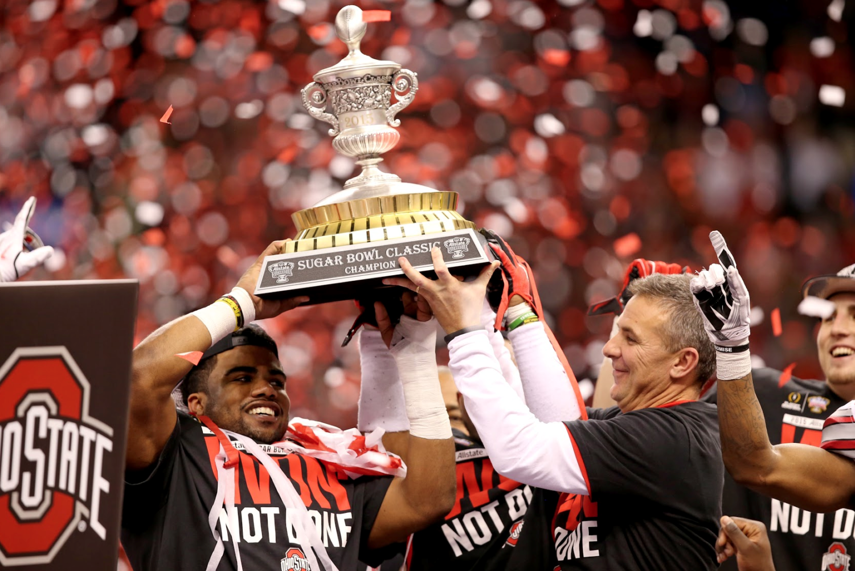 Running back Ezekiel Elliott (left) and coach Urban Meyer (right) lifting the 2015 Allstate Sugar Bowl trophy.
