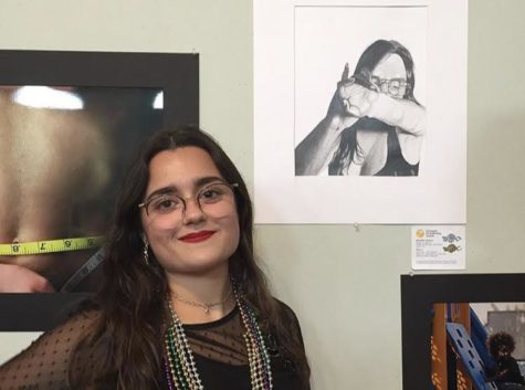 Melanie Cilella posing next to her art at the Scholastic Art and Writing Awards in West Palm Beach, Fla. where she won two gold keys, two silver keys and three honorable mentions in the category of drawing and illustration.
