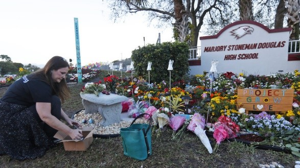 """Suzanne Devine Clark, an art teacher at Deerfield Beach Elementary School, placing hand-painted stones at the Marjory Stoneman Douglas """"Project Grow Love"""" memorial on the Anniversary of the school shooting."""