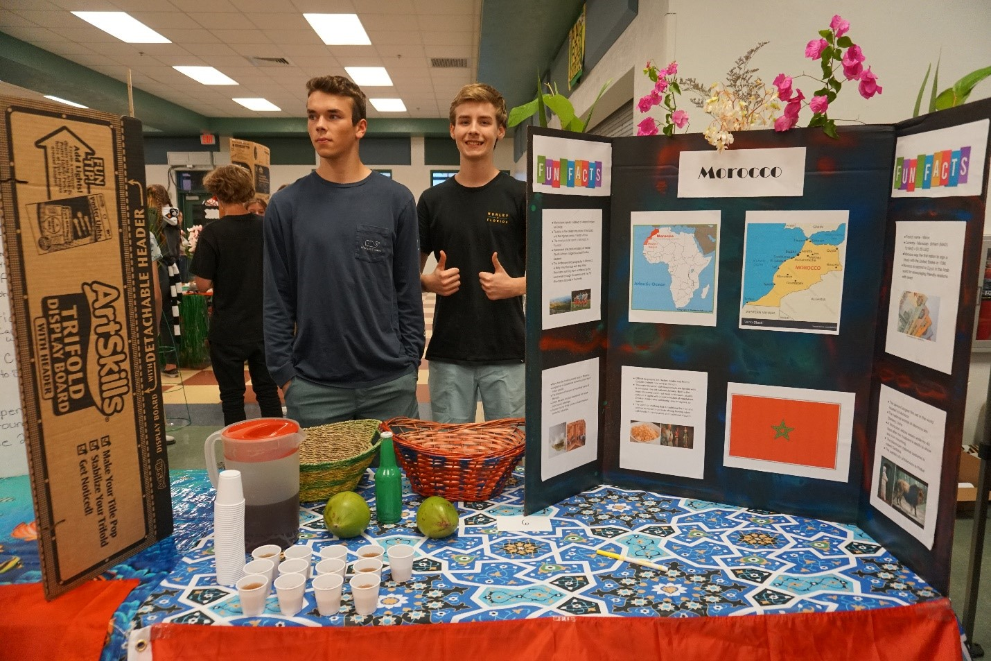 Sophomore Robert Miller and sophomore Dainius Horan standing at their project booth at Mardi Gras.