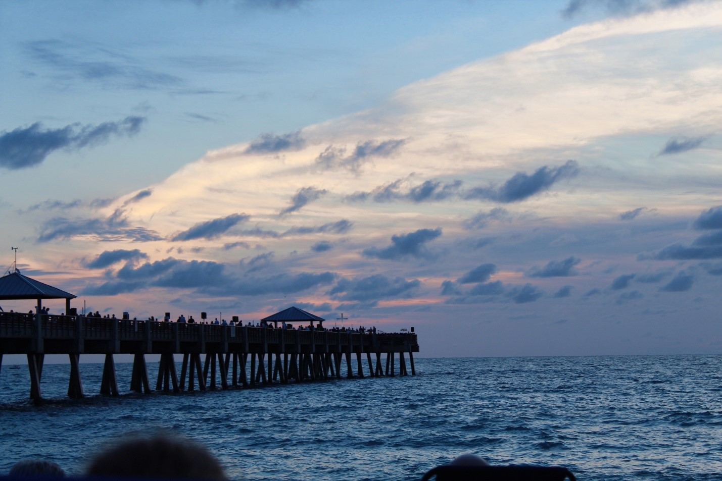 The sun rises as the pastor delivers his message at the end of the pier on Easter Sunday. March 31