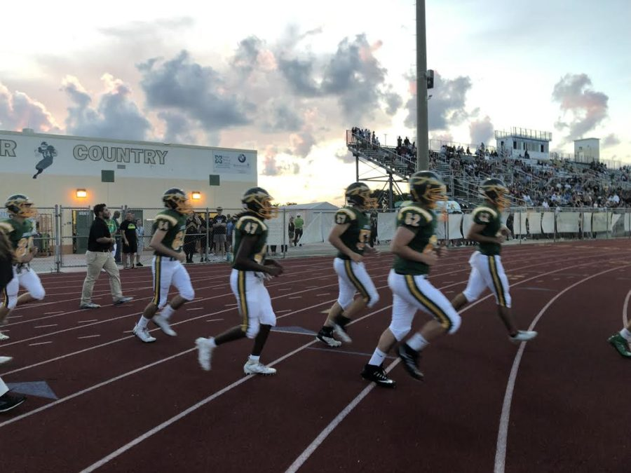 Football players running onto the field after halftime.