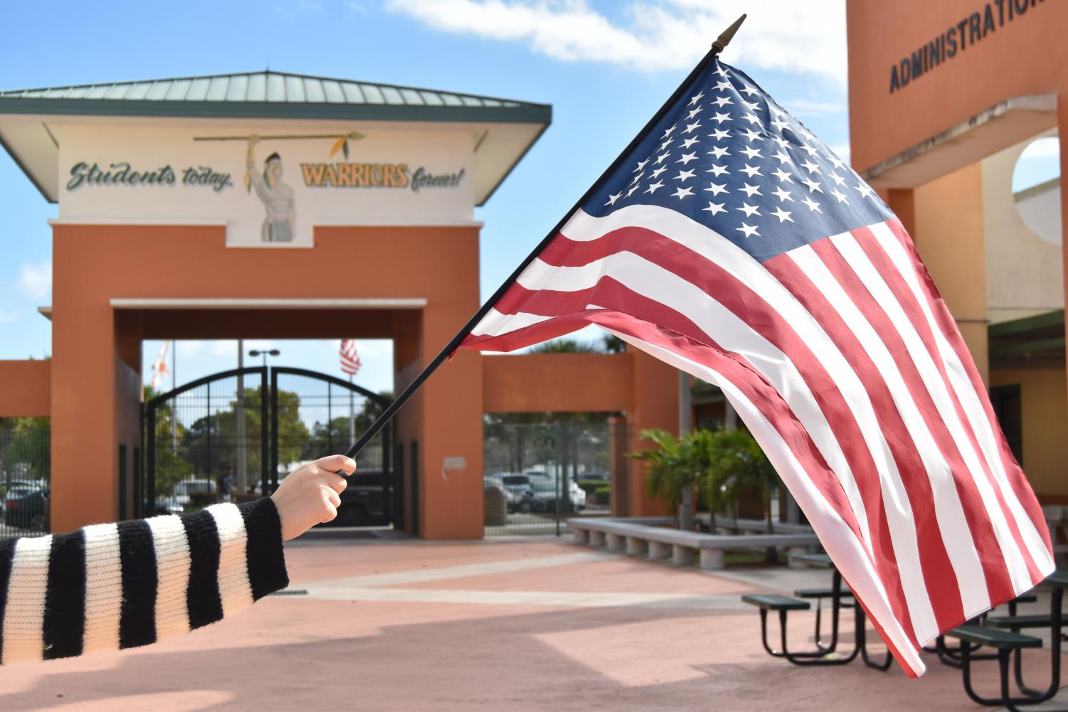 JHS Student waving the American flag at the school's entrance.