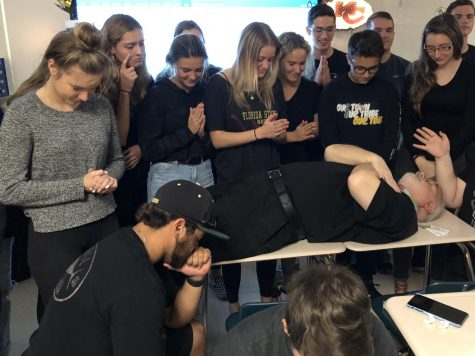John Day pretending to be dead surrounded by his third hour AP Literature students who he asked to wear black.