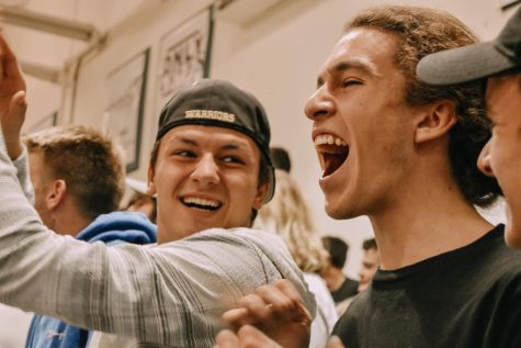 Seniors Josh Devore and Duncan Dyer cheer for the varsity boys basketball team.