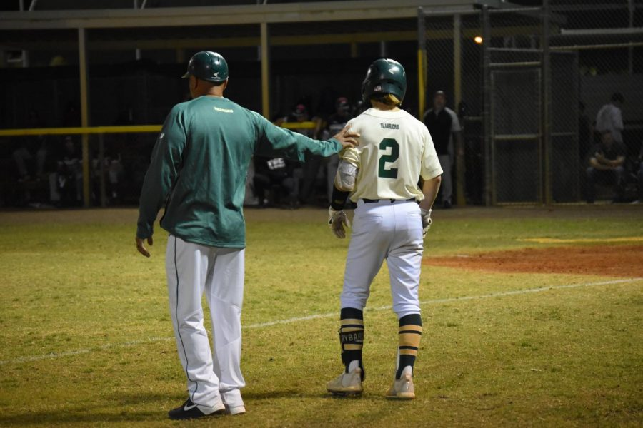 A varsity baseball coach encourages a player at the home game on March 6.
