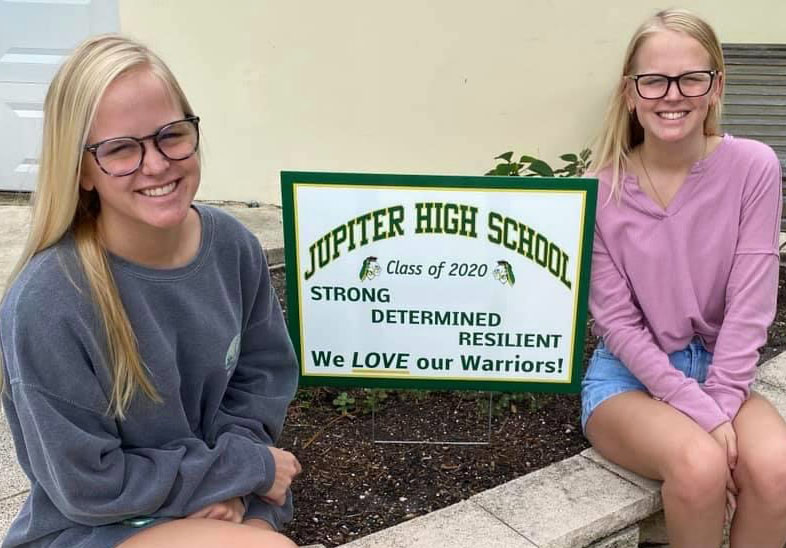 Delaney and Madison Cook, JHS seniors, display their new yard sign supporting the class of 2020 on April 26.
