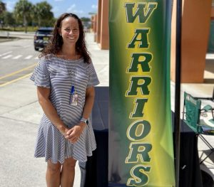 Assistant Principal Kelly Foss waits to greet seniors in JHS drop-off loop, as they pick up their grad bags, on May 21.