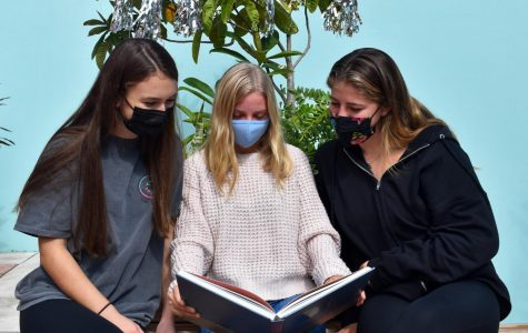 Megan Palmieri, Sydney Buck and Leila Glowka, the editors of the 2021 Chieftain yearbook, peruse the 2020 yearbook after it was honored as an FSPA All-Florida publication.